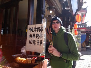 Jonny Blair trying barbecued food in Shuhe Old Town Yunnan China