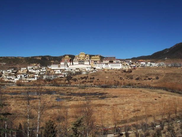 Jonny Blair living a lifestyle of travel at the impressive Ganden Sumtseling Gompa in Yunnan