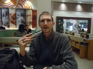 Jonny Blair in Hong Kong using chopsticks