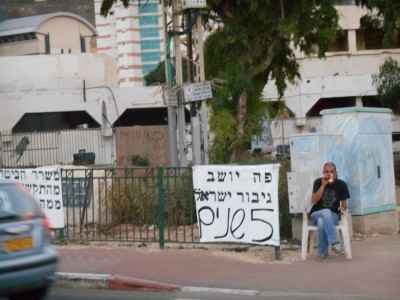 Shomi sits by his protest banners in Haifa