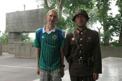 Posing with a North Korean soldier.
