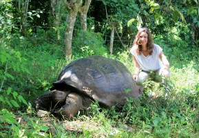 Annette White with a giant tortoise in the Galapagos Islands, Ecuador.