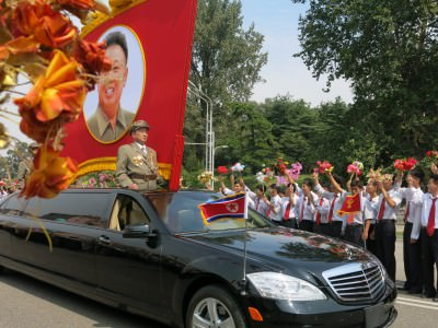 A Kim Jong Il flag on one of the first cars that came past