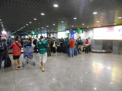 Arrival in Fortaleza - the wee screen beside the luggage belt is showing Iran v. Nigeria.