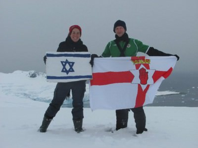 Backpacking Buddies - Israel and Northern Ireland flags flying at Cuverville, Antarctica.