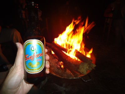 Safari beer and fire at night in the African jungle.