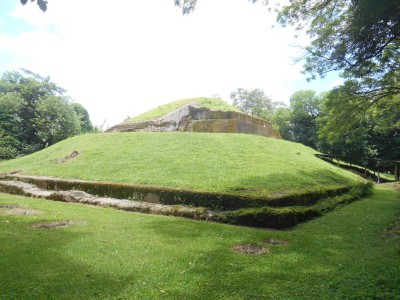 Lots of grass has grown over this pyramid structure.