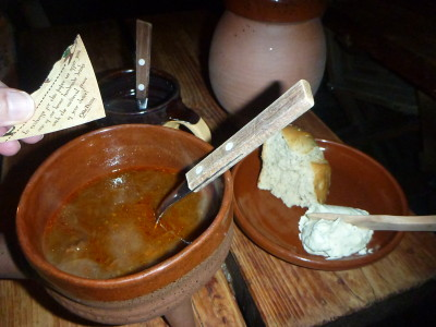 Wild boar and lamb soup with bread and cheese and a hot apple ginger drink in Olde Hansa