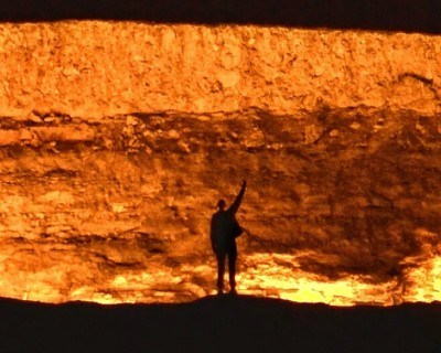 World Traveller Graham Askey sacrificing a bottle of beer to the Darvaza gas crater in Turkmenistan