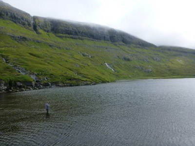 A fisherman fishes in the lake at Saksun