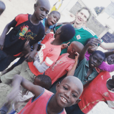 Jonny Blair playing football with kids in Africa